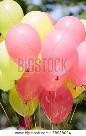 pink and yellow balloons with golden strings.