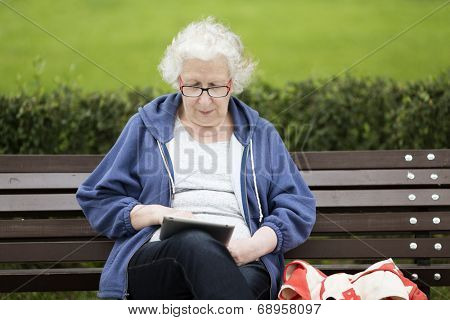 Senior woman with tablet PC on the street.