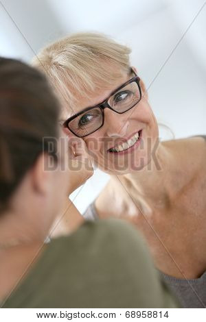 Senior woman trying new eyeglasses in optical store