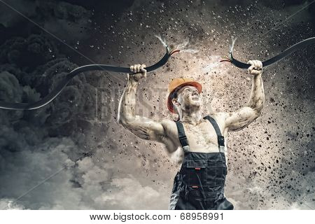 Strong man in uniform tearing electricity cable with hands