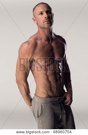 Man with chiseled chest and abs standing confidently on white background