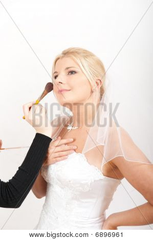 Young beautiful bride applying wedding make-up
