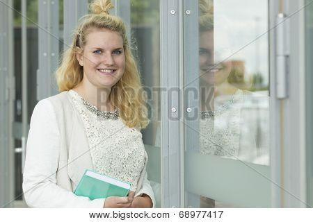 Student Smiles With A Book In Her Hands