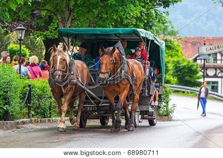 HOHENSCHWANGAU, GERMANY - 19 JUNE 2014: Tourists on a horse-drawn carriage at the Neuschwanstein Castle in Hohenschwangau, Germany. Hohenschwangau is a village located between two popular castles.
