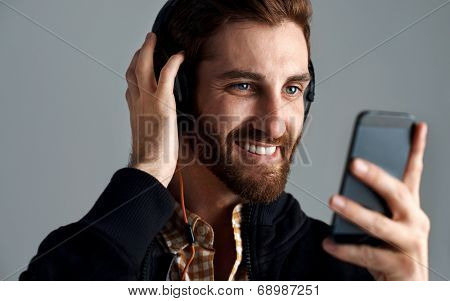 Man with headphones streaming music online with phone enjoying song with beard