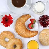stock photo of bagel  - Set table with breakfast bagels marmalade coffee and orange juice from above - JPG