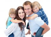 image of piggyback ride  - Portrait Of Family Enjoying Piggyback Ride against a white background - JPG
