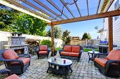pic of grass area  - Backyard cozy patio area with wicker furniture set and brick fireplace - JPG