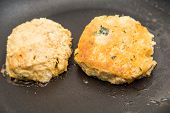 picture of patty-cake  - Fresh crab cakes browning in hot oil in a pan - JPG