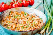 picture of chanterelle mushroom  - fried chanterelle mushrooms with green onions in a frying pan on rustic background - JPG