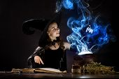 foto of sorcery  - Little Halloween witch reading conjure above pot - JPG