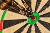 Success hitting target aim goal achievement concept background - three darts in bulls eye close up poster