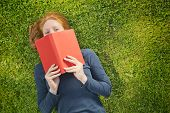 stock photo of peek  - Playful college or university student lies on her back over green grass in a park or on campus with a red book in her hands - JPG