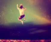 picture of jumping  -  a boy jumping of an old train trestle bridge into a river done with a retro vintage instagram filter  - JPG