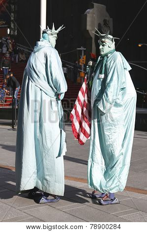 Only in New York. Unidentified street performers dressed as a Statue of Liberty at Times Square