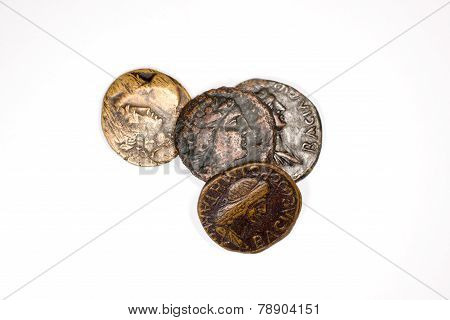 Four Old Coins With Portraits Of Emperors On A White Background