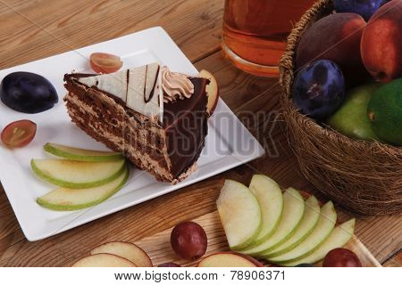 slice of chocolate cream brownie cake topped with white chocolate and cream flowers with hot tea mug decorated with fruits apple plum and grape on plate on wooden table