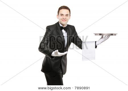 A young butler carrying an empty tray