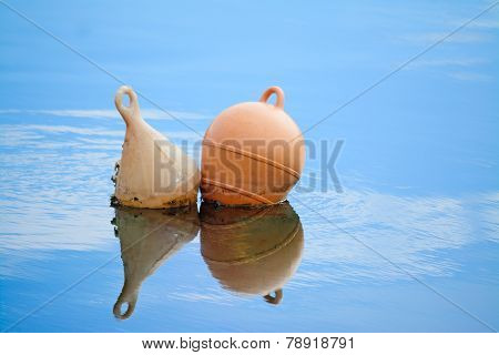Two Buoys Reflected In The Water