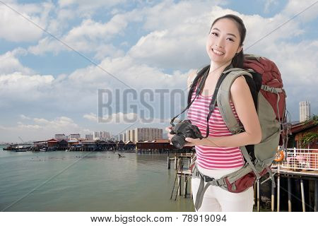 Happy smiling Asian young female backpacker with camera in Penang, Malaysia.