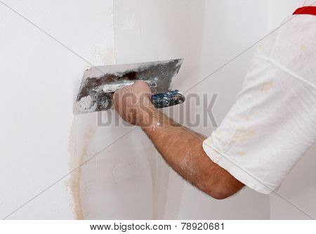 Worker Repairing Plaster To Wall