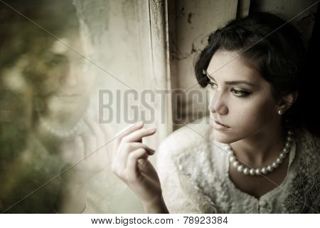 Gorgeous brunette woman with brown eyes wearing pearls looking through the window portrait