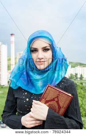 beautiful muslim woman wearing hijab and holding holy book Koran