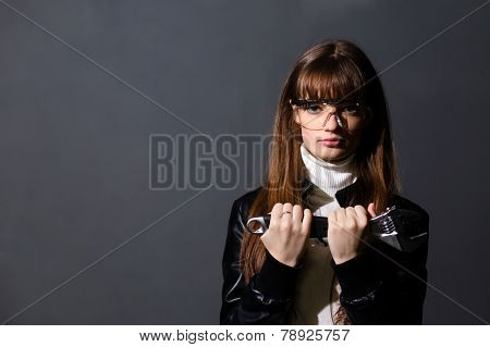Young Women In Safety Glasses With Adjustable Wrench On A Dark Background
