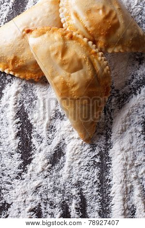 Empanadas On A Table With Flour Spills. Vertical Top View