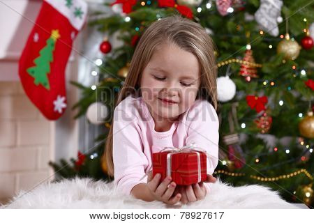 Little girl lying with gift on fur carpet on Christmas tree background