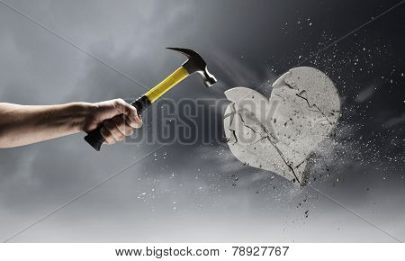 Close up of hammer in human hand breaking stone heart