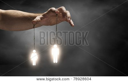 Close up of human hand and people hanging on fingers
