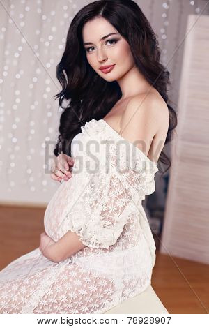 Beautiful Pregnant Woman With Long Dark Hair Posing In Cozy Interior