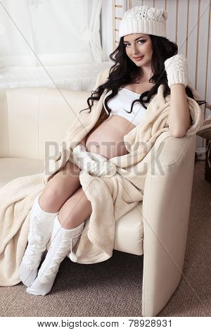Beautiful Pregnant Woman With  Dark Hair Wearing Warm Knitted Clothes