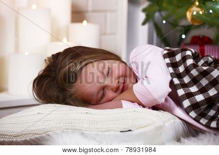 Little girl sleeping on fur carpet on fir tree and fireplace with candles background