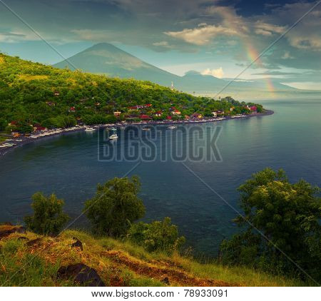 Calm lagoon with buildings on the coastline and volcano on the horizon. Bali, Indonesia