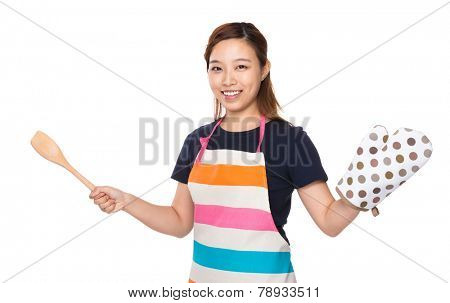 Housewife hold with wooden ladle and oven gloves