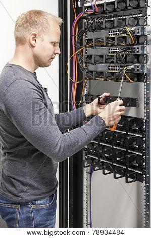 IT engineer builds network rack in datacenter