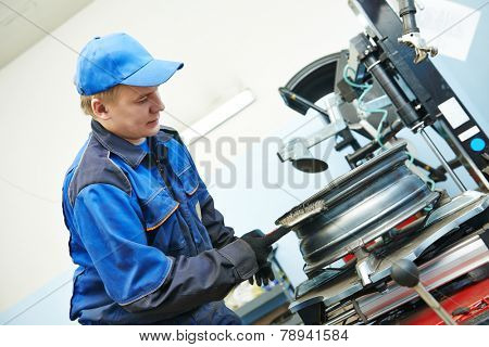 Auto repairman cleaning automobile car wheel rim at tyre fitting machine during tire replacing