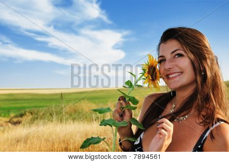 Beautiful Girl In A Field Holding Sunflower