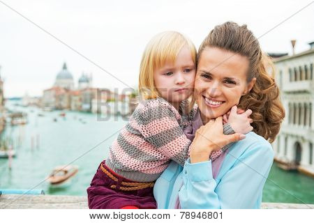 Mother And Baby Girl Hugging On Bridge With Grand Canal View In Venice, Italy
