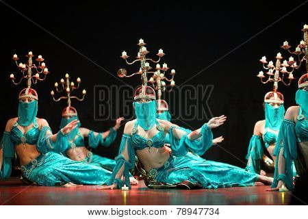 MOSCOW, RUSSIA - APR 26, 2014: Beautiful women in green dress dance with candelabras on heads in art cafe Durov