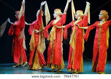 MOSCOW, RUSSIA - APR 26, 2014: Beautiful women in red dress dancing with scarves in a line on stage at the art cafe Durov
