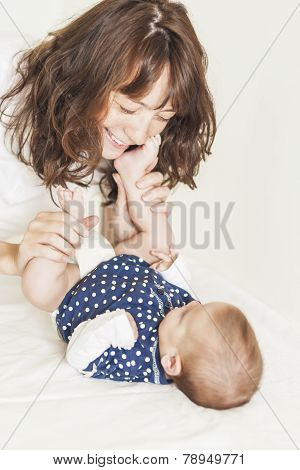 Young And Happy Mother Having Good Time Together With Her Baby Infant