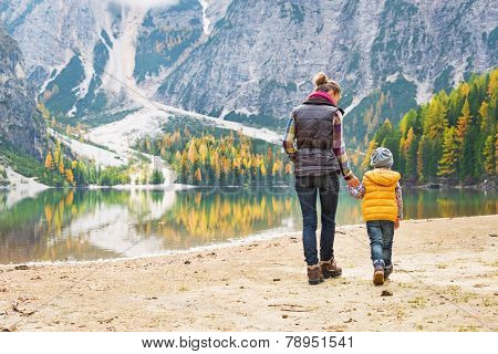 Mother And Baby Walking On Lake Braies In South Tyrol, Italy. Rear View