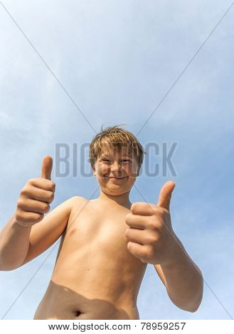 Happy Smiling Young Boy  Gives Fingersign Thumbs-up