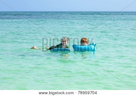 Boys Swim In The Ocean With Air Matress And Have Fun