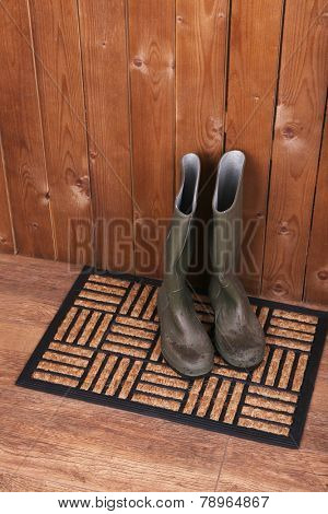 Dirty wellington boots on door mat in room