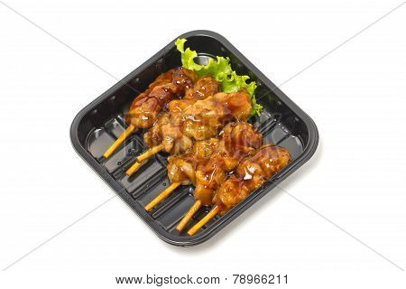 Chicken Teriyaki With Skewers Inblack Tray Isolated On White.