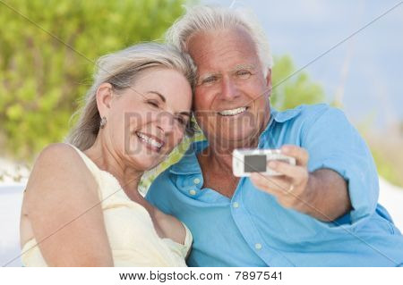 Happy Senior Couple Taking Photographs On Cell Phone At Beach
